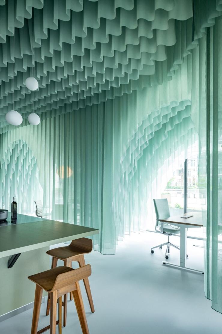 Kantoorontwerp van Beyond Space met golvende gordijnen weerspiegelt het Amsterdamse IJ